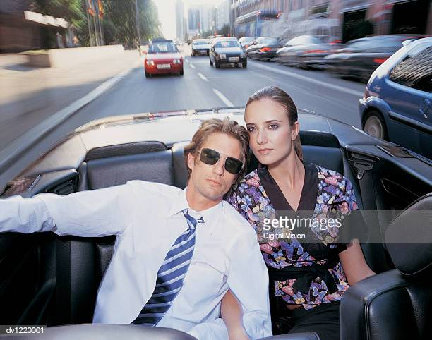Portrait of a Business Couple Sitting in the Back Seat of a Convertible Car