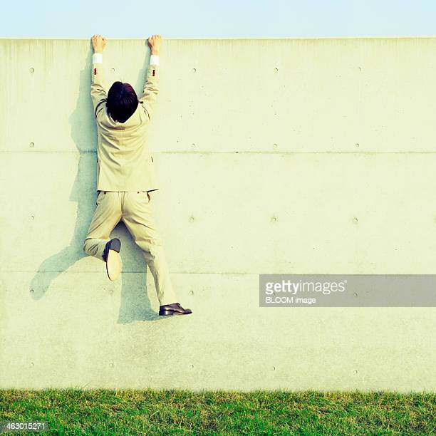 portrait of a business man climbing on wall - hanging stock pictures, royalty-free photos & images