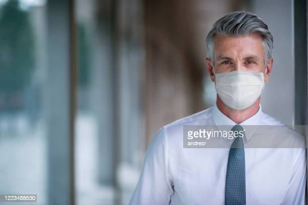 portrait of a business man wearing a facemask at the office - protective face mask stock pictures, royalty-free photos & images
