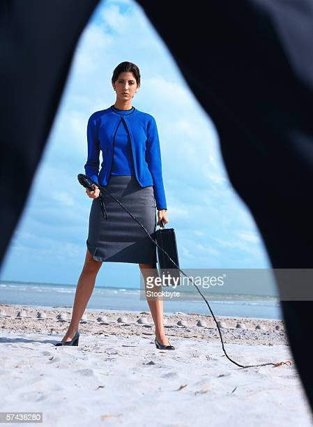 portrait of a business woman carrying a briefcase and holding a whip - women whipping men stock photos and pictures