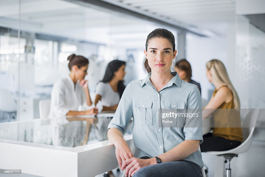 Portrait of a business woman sitting at desk : Stock Photo