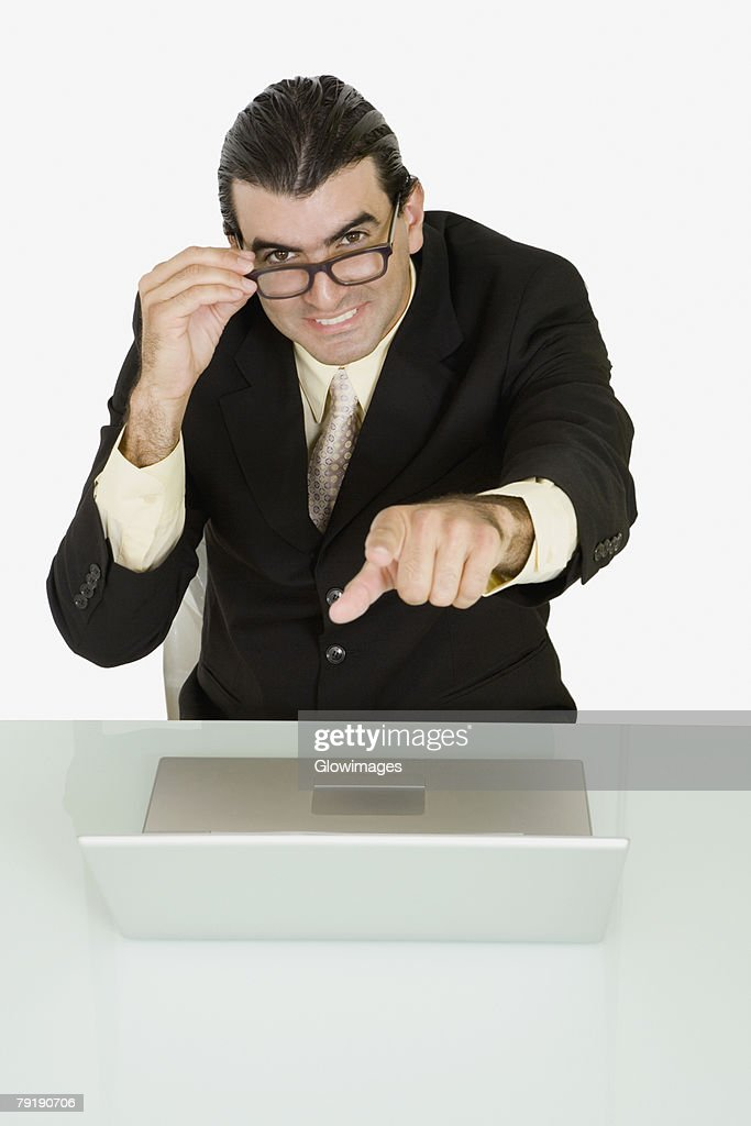 Portrait of a businessman adjusting his eyeglasses and pointing forward : Foto de stock