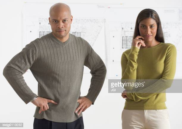 portrait of a businessman and a businesswoman standing - arms akimbo stock pictures, royalty-free photos & images