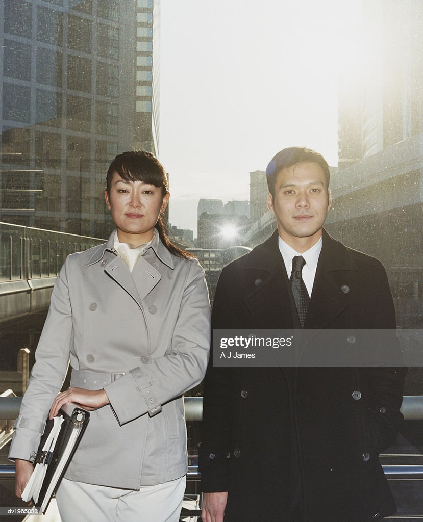 Portrait of a Businessman and Businesswoman Standing on a Footbridge : Stock Photo