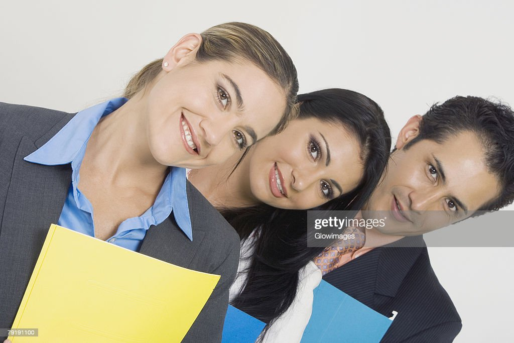 Portrait of a businessman and two businesswomen smiling and holding files : Foto de stock