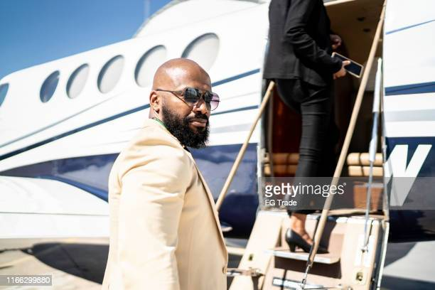 portrait of a businessman boarding into a corporate jet - best sunglasses for bald men stock pictures, royalty-free photos & images