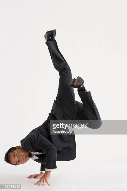 portrait of a businessman doing a handstand - posing shoes ストックフォトと画像