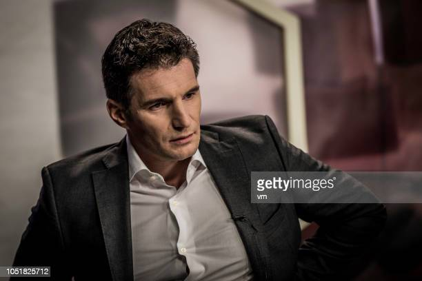 portrait of a businessman during a tv show interview - television show stock pictures, royalty-free photos & images