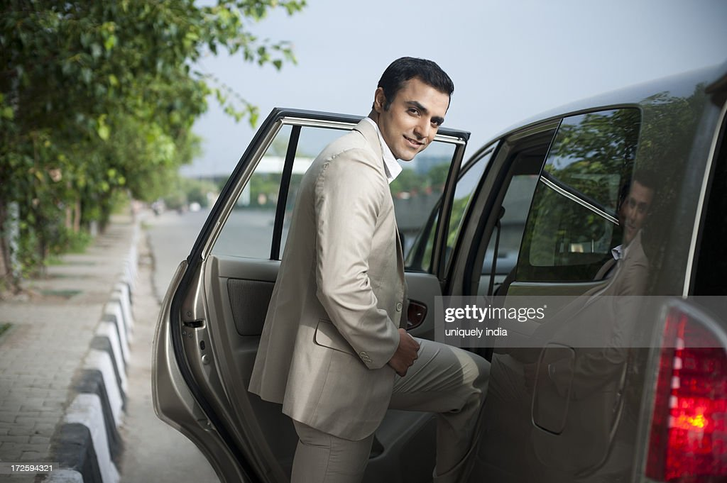 portrait of a businessman getting into a car and smiling stock photo getty images. Black Bedroom Furniture Sets. Home Design Ideas