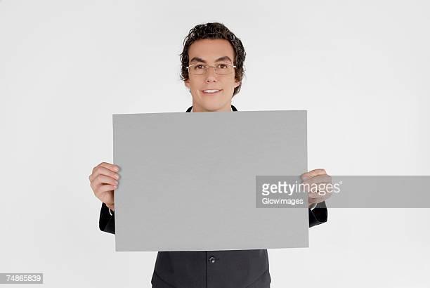 Portrait of a businessman holding a blank placard