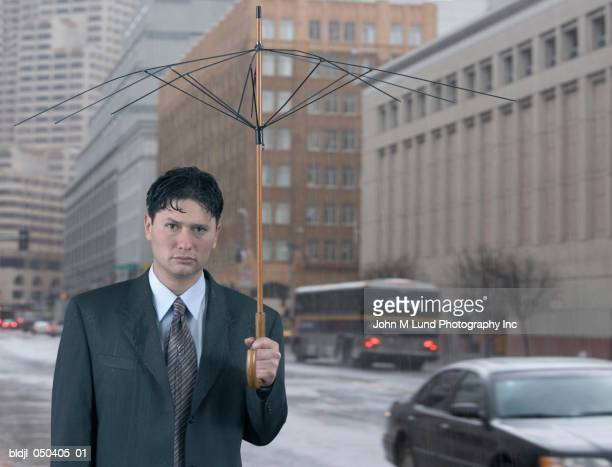 Portrait of a businessman holding a broken umbrella