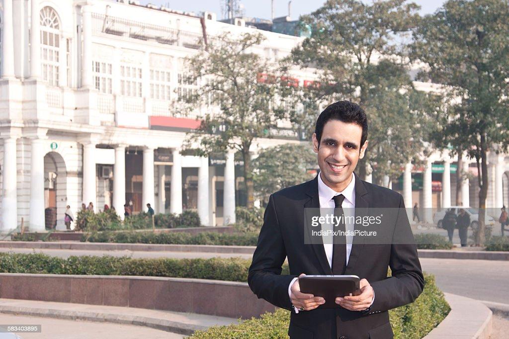 Portrait of a businessman holding a digital tablet , INDIA , DELHI : Stock Photo