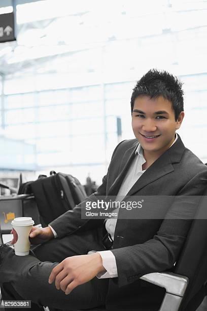 Portrait of a businessman holding a disposable glass