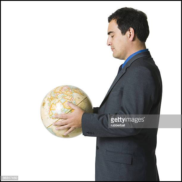 portrait of a businessman holding a globe - world at your fingertips stock pictures, royalty-free photos & images