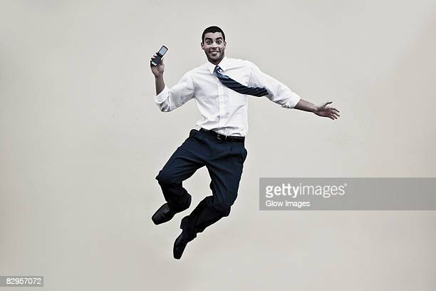 Portrait of a businessman holding a mobile phone and jumping