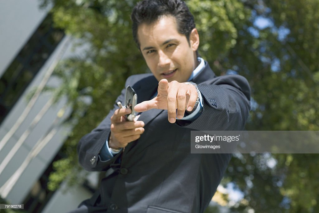Portrait of a businessman holding a mobile phone and pointing forward : Stock Photo