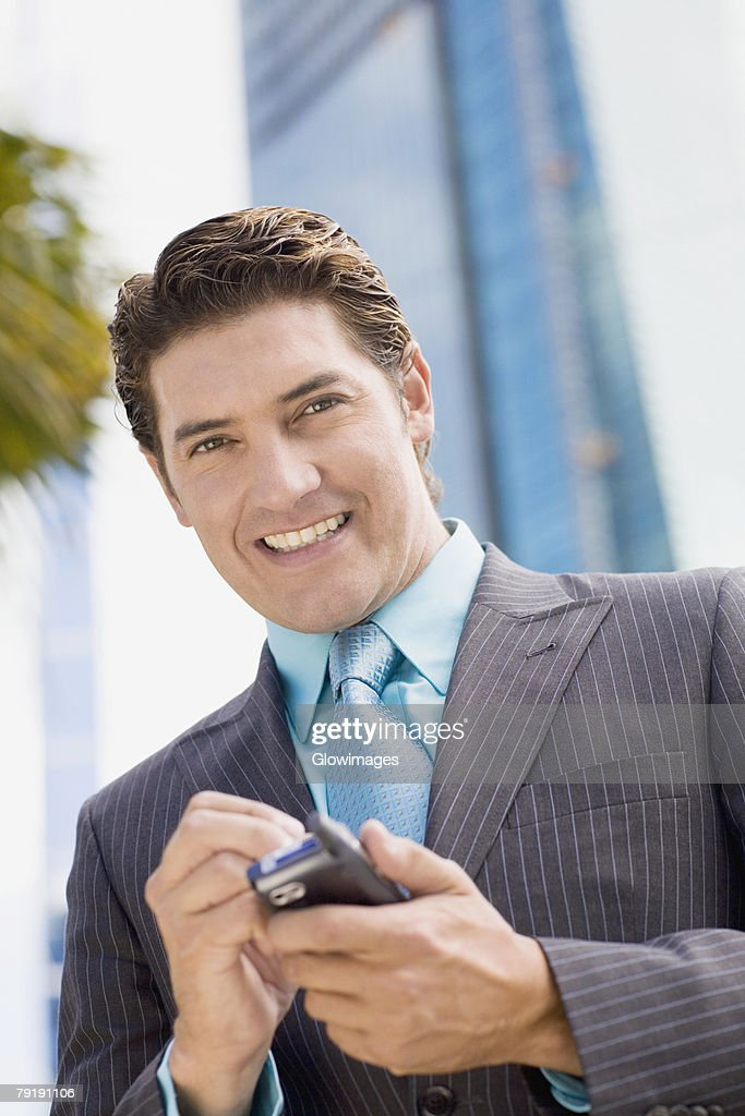Portrait of a businessman holding a mobile phone and smiling : Stock Photo