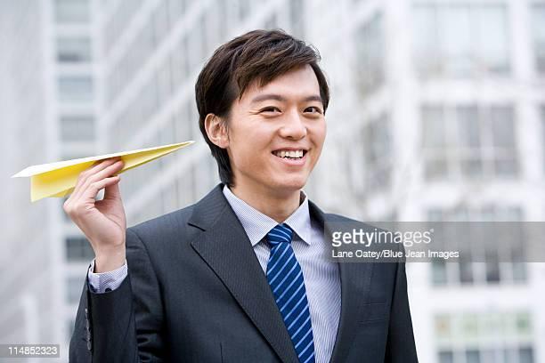 Retrato de un hombre de negocios sosteniendo un avión de papel
