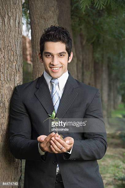 Portrait of a businessman holding a plant and smiling