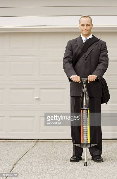 Portrait of a businessman holding a pogo stick