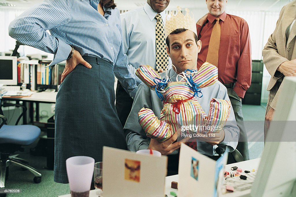 Portrait Of A Businessman Holding His Birthday Gift In The Office Stock Photo