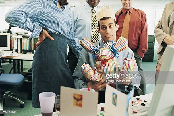 portrait of a businessman holding his birthday gift in the office - delusione foto e immagini stock