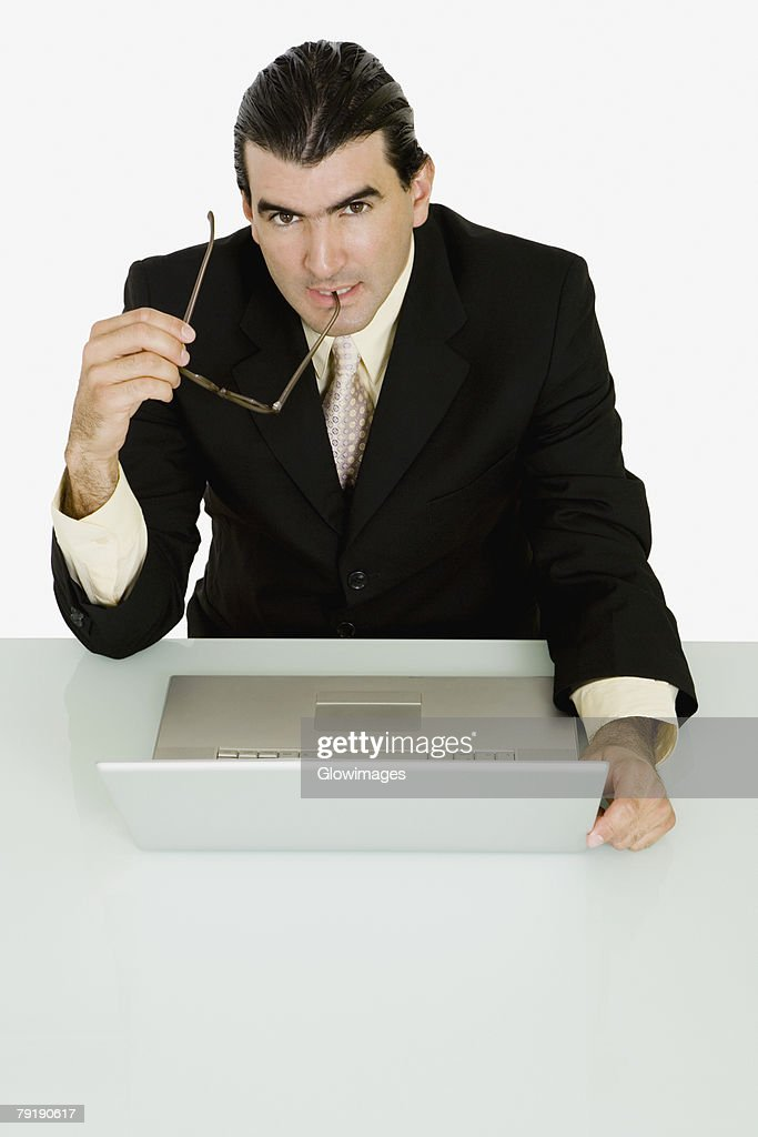 Portrait of a businessman holding his eyeglasses and thinking : Foto de stock