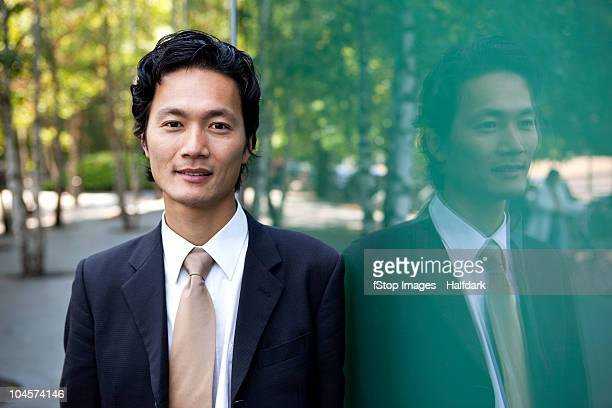 portrait of a businessman leaning against a window, outdoors - 30代 ストックフォトと画像