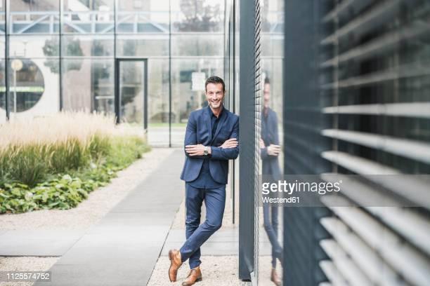 portrait of a businessman leaning on a wall, smiling - bras croisés photos et images de collection