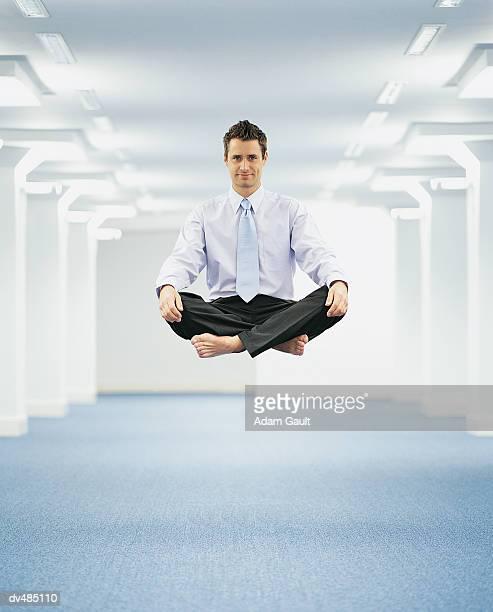 Portrait of a Businessman Levitating in an Open Plan Office