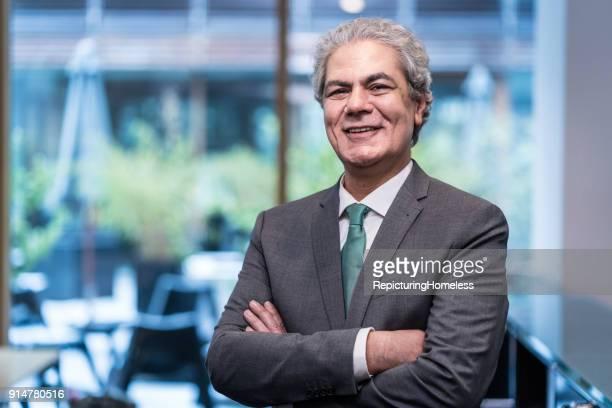 Portät eines Geschäftsmannes der mit verschränkten Armen und einem Lächeln in die Kamera schaut