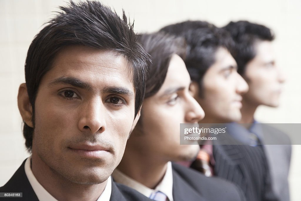 Portrait of a businessman looking serious with three business executives behind him : Stock Photo