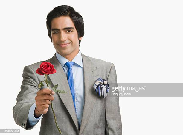 Portrait of a businessman offering a red rose