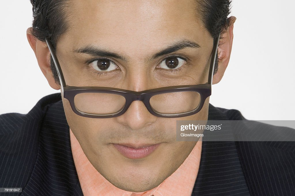 Portrait of a businessman peeking over his eyeglasses : Foto de stock