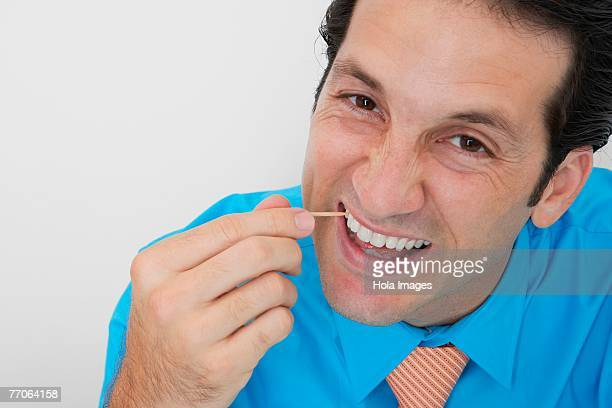 Portrait of a businessman picking his teeth in an office