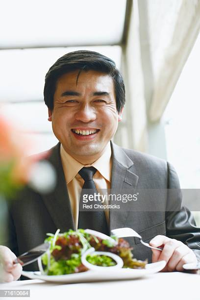 Portrait of a businessman seated at the table in a restaurant smiling