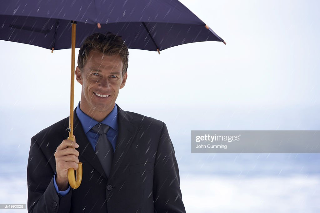 Portrait of a Businessman Sheltering Underneath an Umbrella in the Rain : Stock Photo