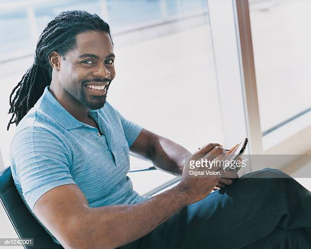portrait of a businessman sitting in a chair and using a handheld pc - dreadlocks stock pictures, royalty-free photos & images