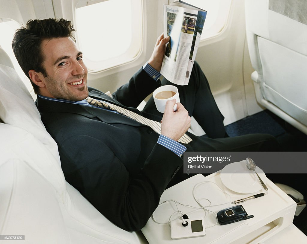 Portrait of a Businessman Sitting in a Plane Holding a Magazine and a Cup of Coffee : Stock Photo