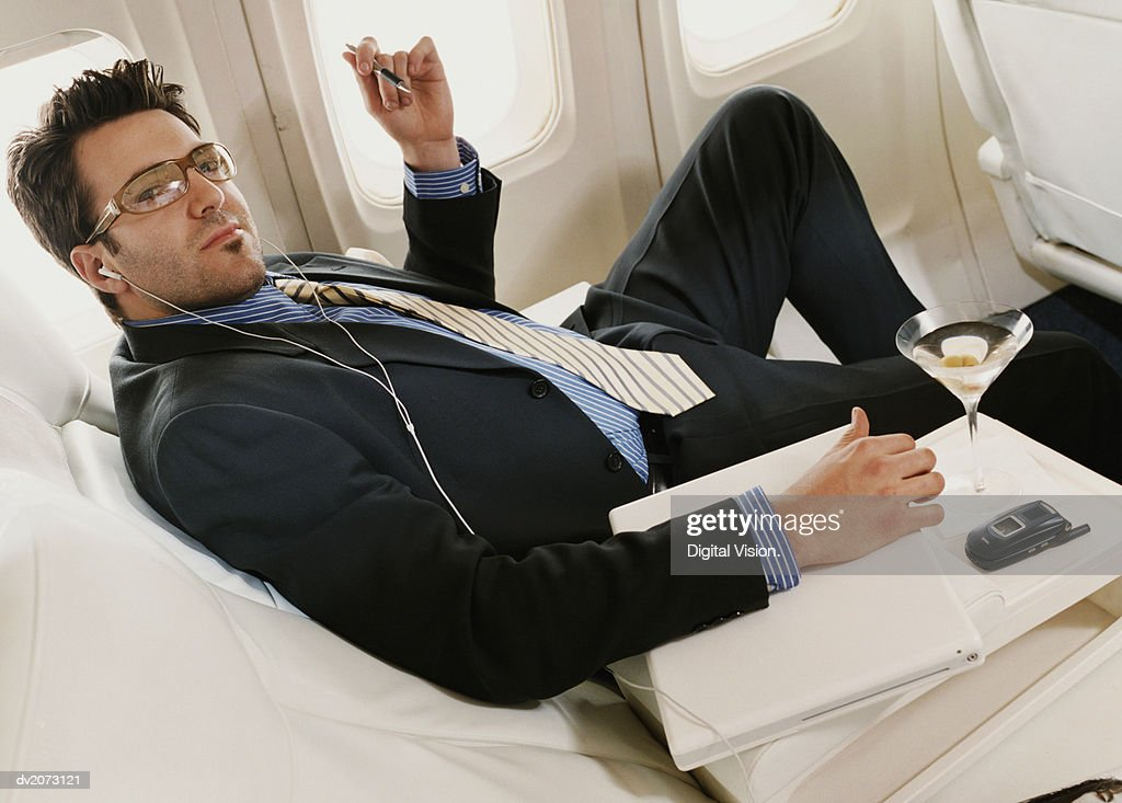 Portrait of a Businessman Sitting in a Plane With a Laptop, Wearing Headphones : Stock Photo