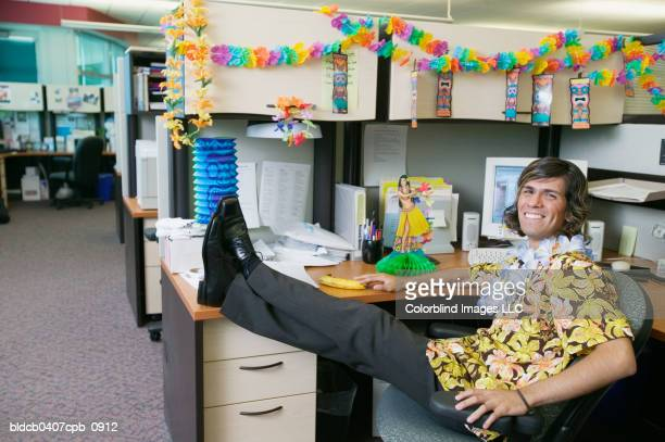 portrait of a businessman sitting on chair in an office - hawaiian shirt stock photos and pictures