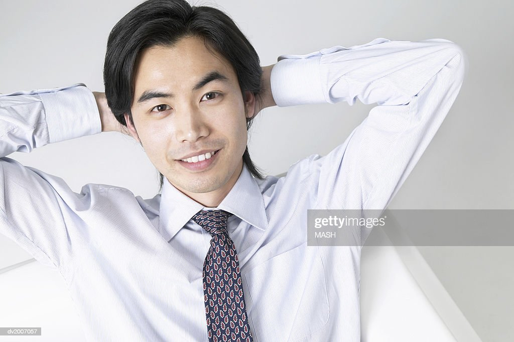 Portrait of a Businessman Sitting With His Hands Behind His Head : Stock Photo