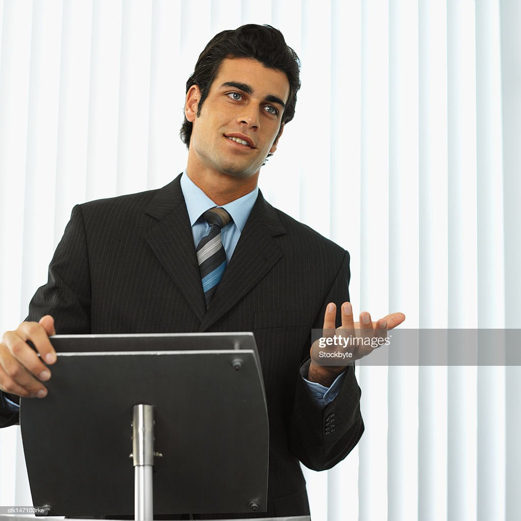 portrait of a businessman standing behind a podium giving a speech : Stock Photo