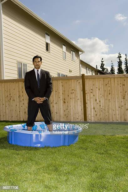 portrait of a businessman standing in a wading pool - rolled up pants stock pictures, royalty-free photos & images