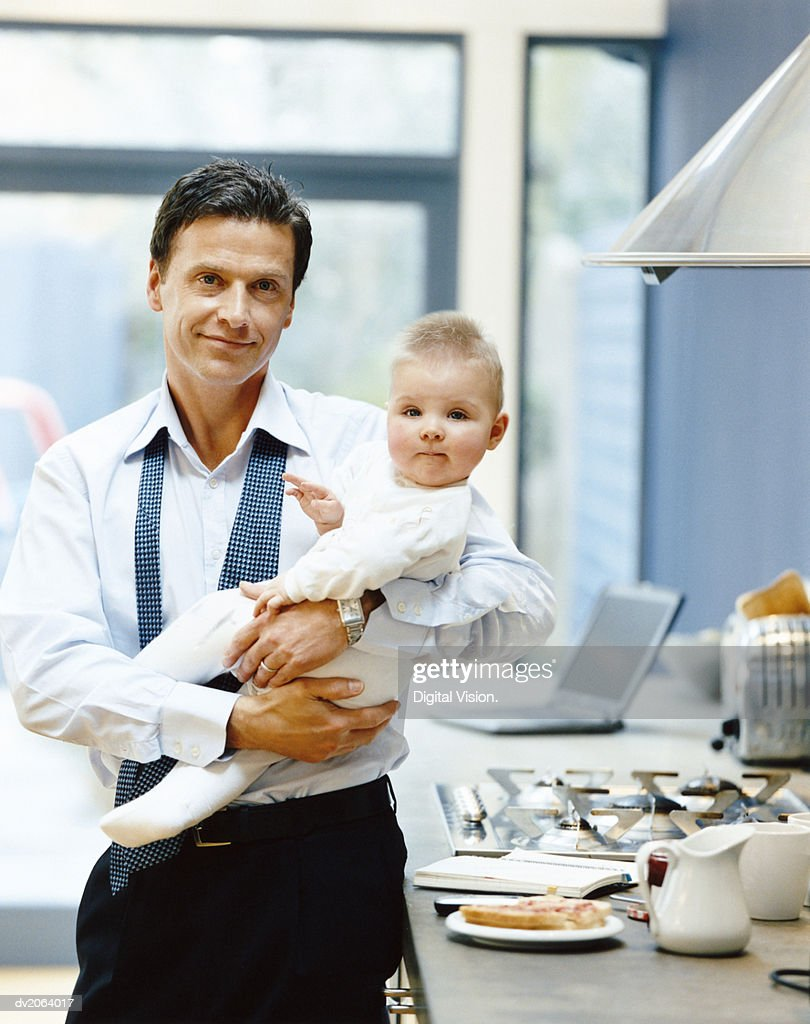 Portrait of a Businessman Standing in the Kitchen Holding a Baby : Stock Photo