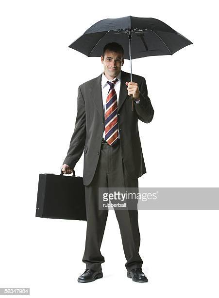 Portrait of a businessman standing with a briefcase and umbrella