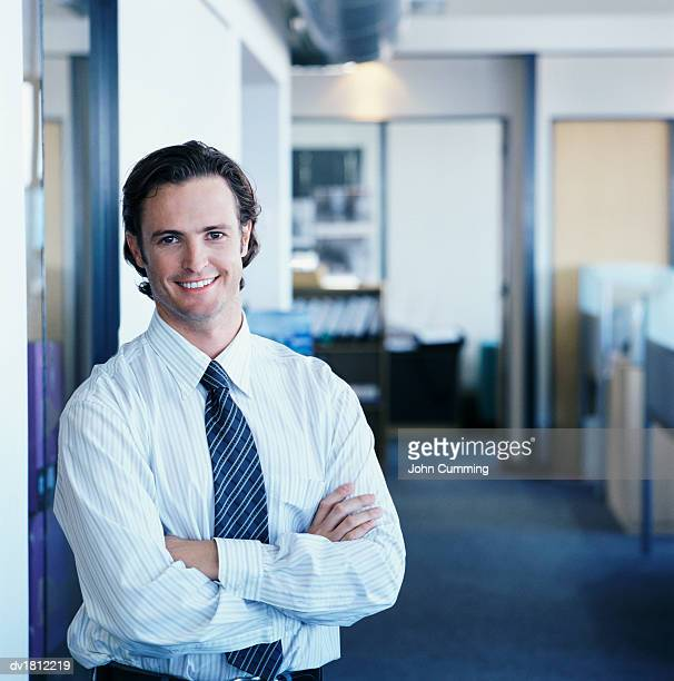 portrait of a businessman standing with his arms crossed in an open plan office - オールバック ストックフォトと画像