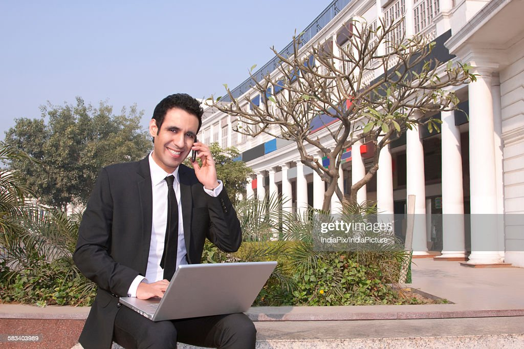 Portrait of a businessman talking on a mobile phone , INDIA , DELHI : Stock Photo