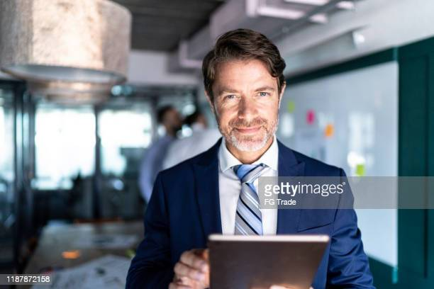 portrait of a businessman using a digital tablet - chief executive officer stock pictures, royalty-free photos & images