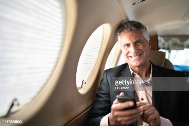 retrato de um homem de negócios que usa o smartphone em um jato confidencial - abundância - fotografias e filmes do acervo